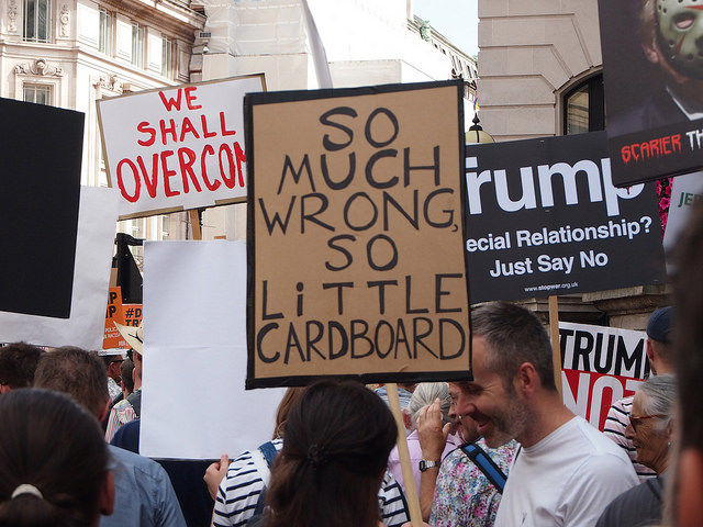 People hold homemade signs and placards against Trump