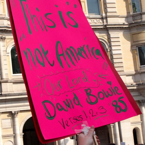 """Pink placard reading """"This is not America - David Bowie"""" is held up in a demonstration crowd."""