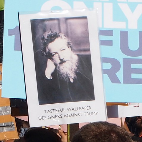 """Homemade banner with the caption """"Tasteful Wallpaper Designers Against Trump"""" with a photo of William Morris."""